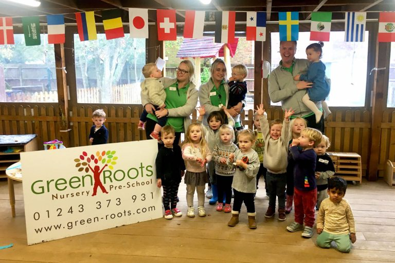Photo of nursery children and staff standing beside the Green Roots logo
